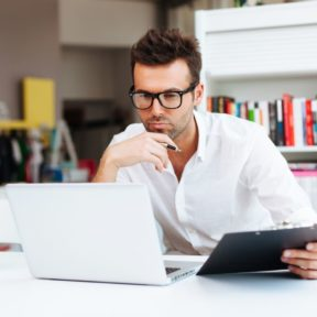 Man studying CELTA online at laptop