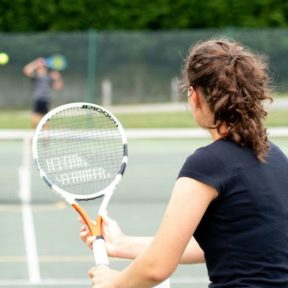 A girl holds a tennis racquet up, preparing to volley the ball served by her opponent