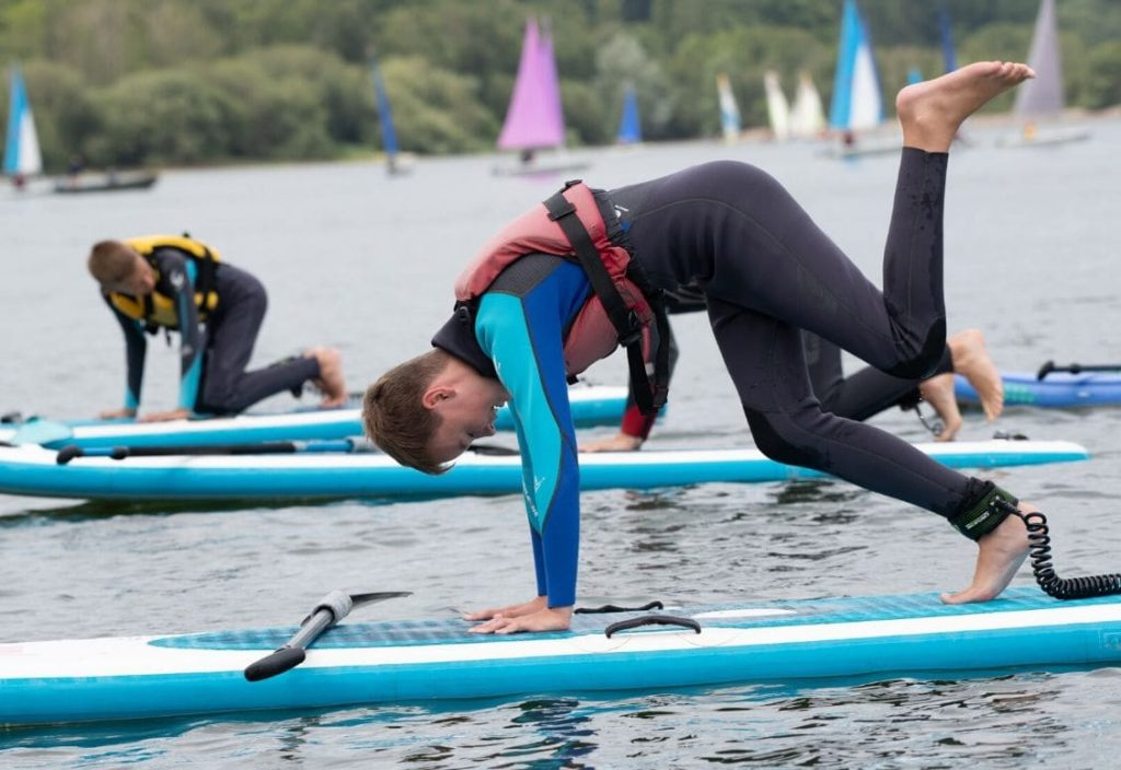 A young boy in a wetsuit balances on a paddleboard in the middle of the lake, with other students doing the same behind him