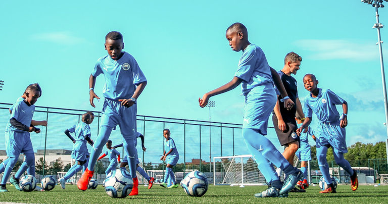 Boys training outdoors on Manchester City Academy pitches