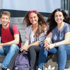 Three smiling students sit on the steps outside the Facebook headquarters in Dublin