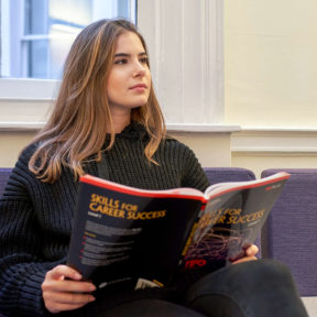 Student at BSC London reading a Skills for Success brochure