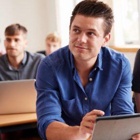 A man in a blue shirt listens to the teacher trainer