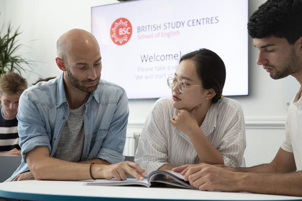 Três estudantes adultos leem juntos um livro didático em sala de aula.