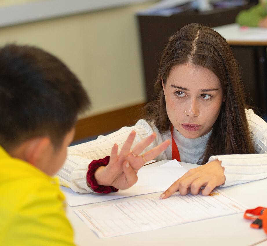 Uma professora contando com um jovem estudante
