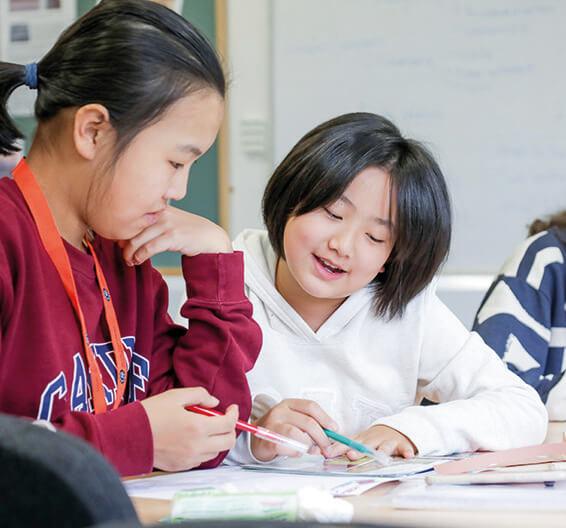 Duas meninas estão discutindo o trabalho delas em uma mesa