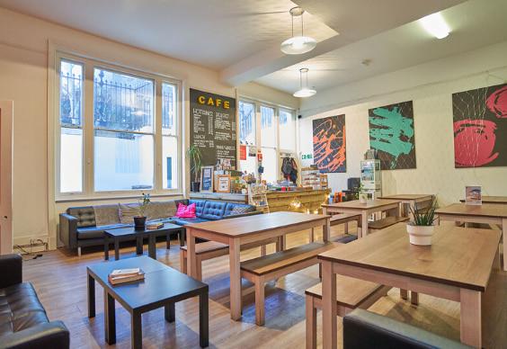 Interior da cafeteria na BSC Londres com bancos de madeira e um quadro negro onde está escrito bebidas quentes e sanduíches
