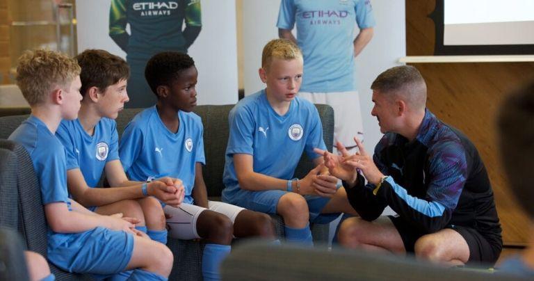 Treinador falando com jovens jogadores durante uma oficina de futebol