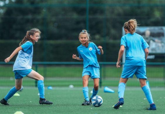 Meninas passando a bola entre elas durante uma sessão de treinamento