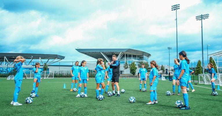 Meninas sendo instruídas pelo treinador durante a sessão de treinamento