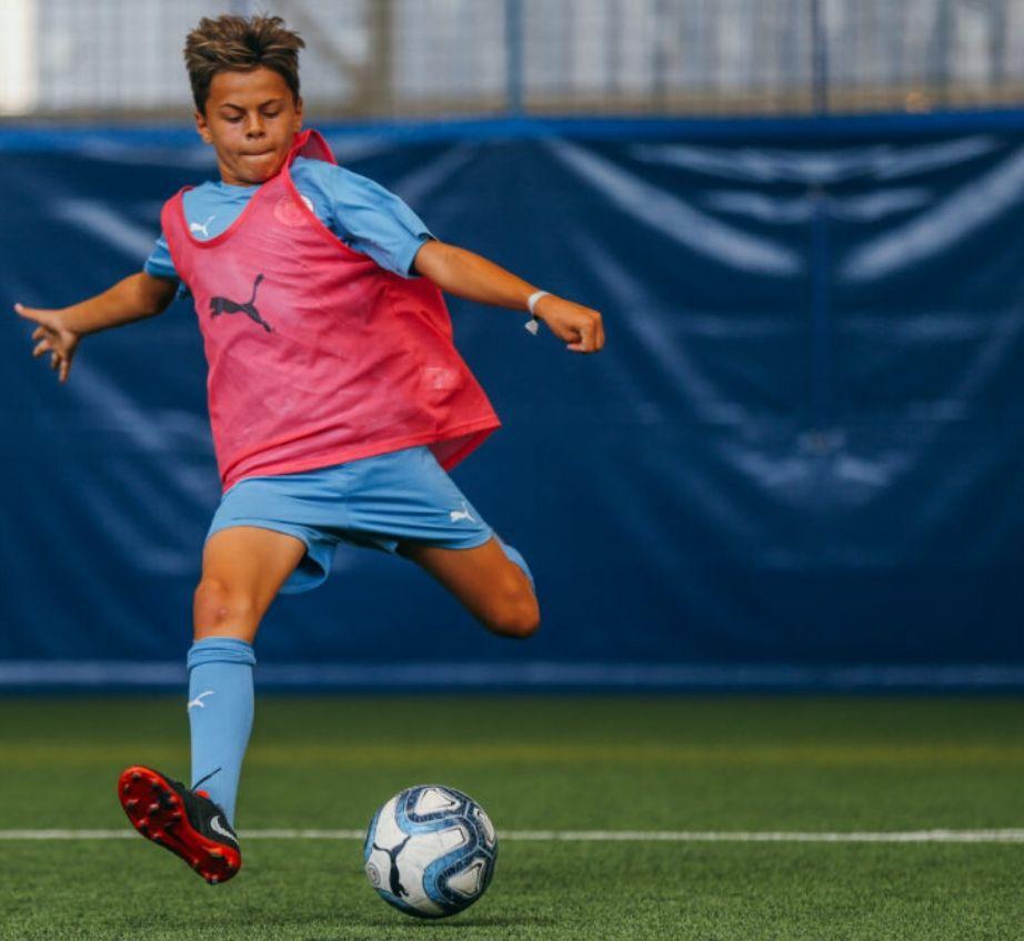 Jogador em posição de chutar para o gol em um campo de futebol coberto