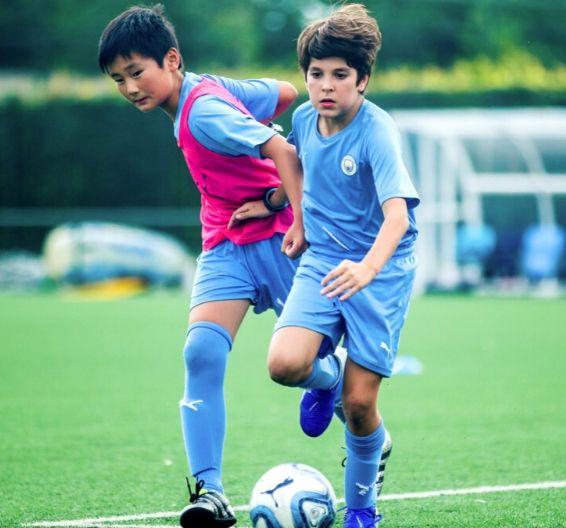 Meninos brigando pela posse de bola em campo de futebol ao ar livre