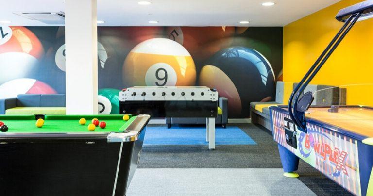 Sala de jogos com mesa de bilhar, air hockey e mesa de pebolim