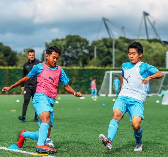 Dois adolescentes jogam futebol e o treinador da Manchester City Academy os observa no fundo
