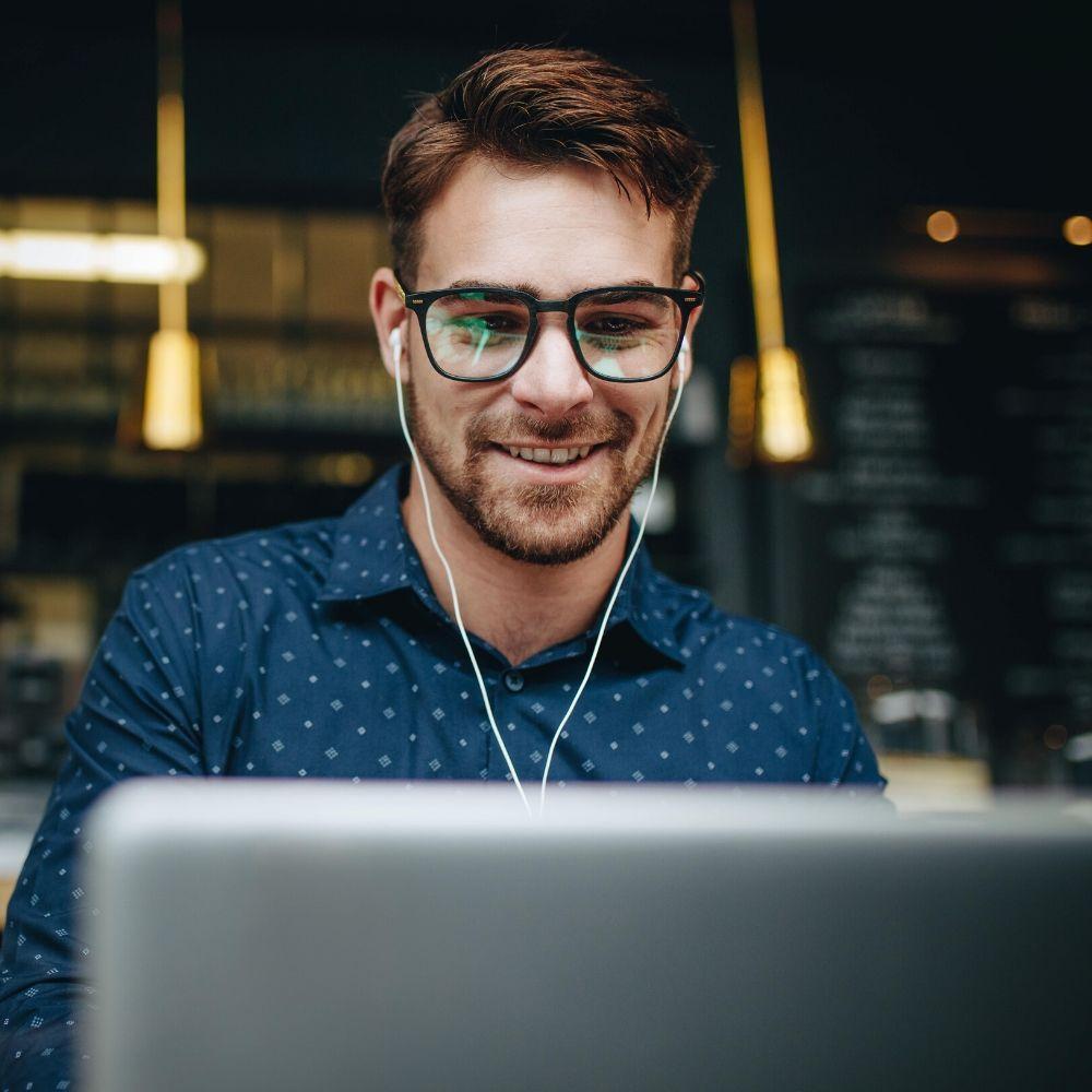Homem vestindo óculos e usando um laptop e fones de ouvido