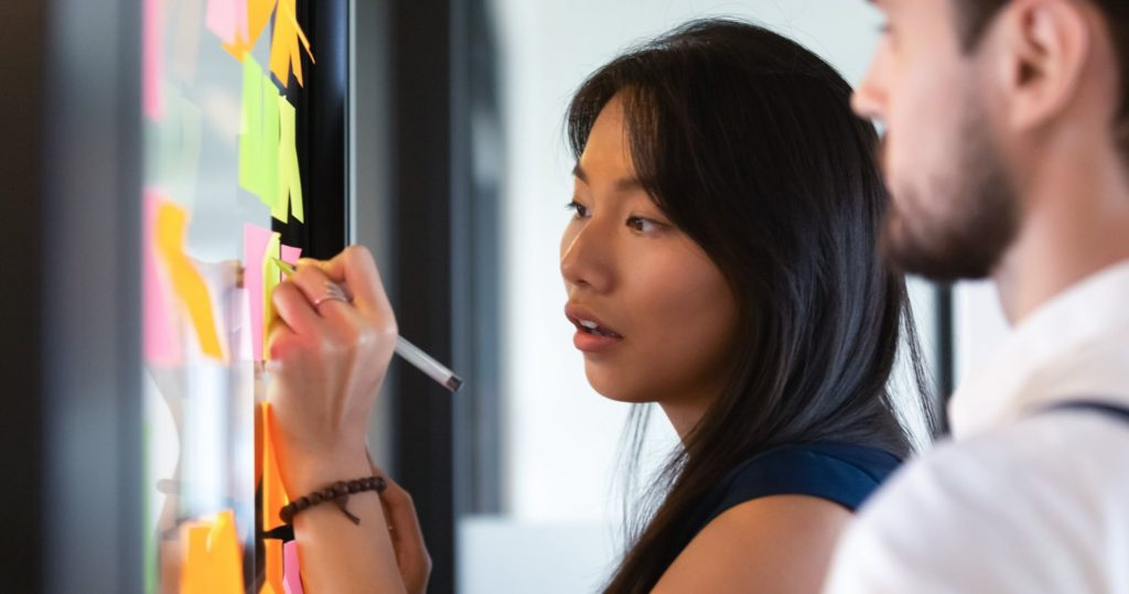 Mulher escrevendo em um quadro com post-its colados