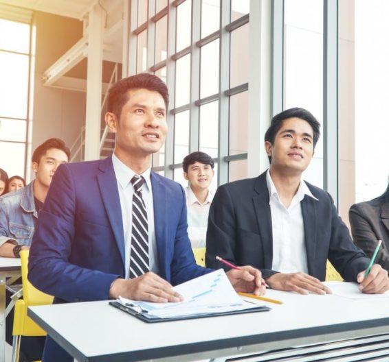 Homem vestindo terno e tomando notas em uma sala de aula
