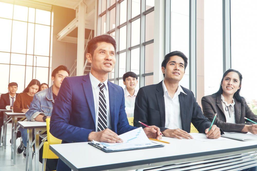 Grupo de homens e mulheres de terno tomando nota em um ambiente de sala de aula
