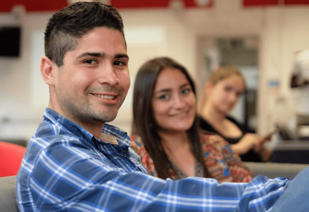 Estudante da BSC em camisa xadrez olhando para a câmera