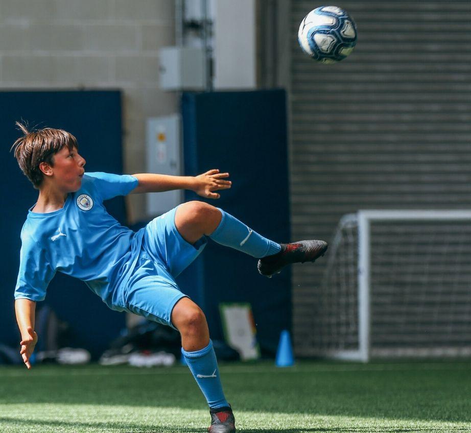 Jogador de futebol tentando dar um pontapé aéreo na quadra coberta