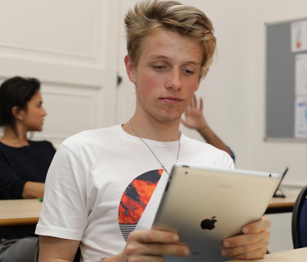 Estudantes em sala usando um iPad com outros estudantes no fundo
