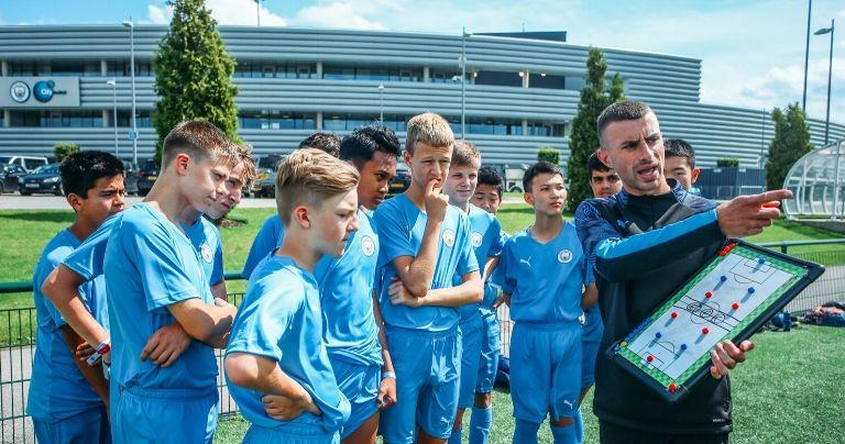 Meninos recebendo instruções do treinador do Manchester City fora do campo