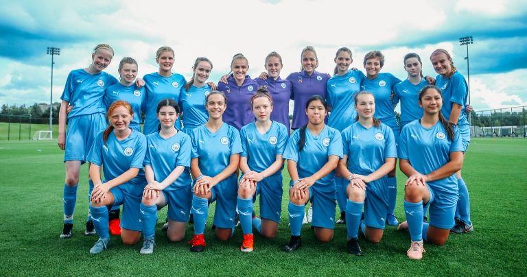 Time de meninas adolescentes posando com jogadoras do time feminino do Manchester City