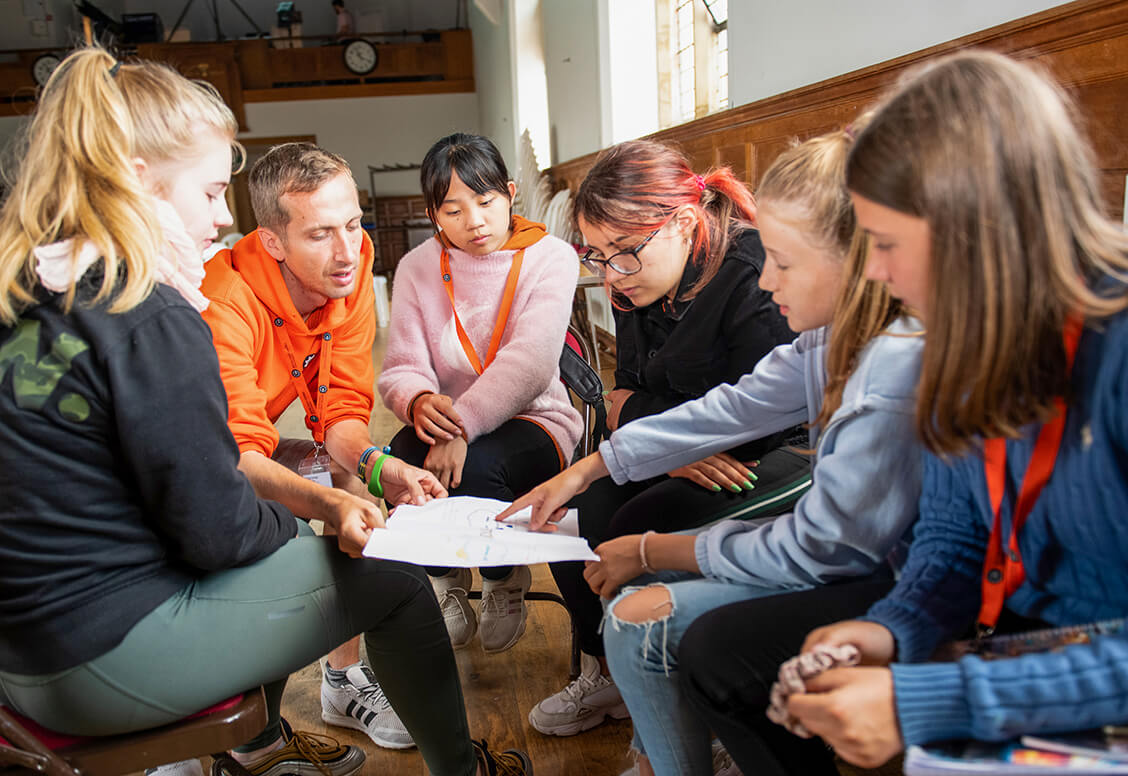 Um grupo de estudantes conversando com um líder de grupo adulto