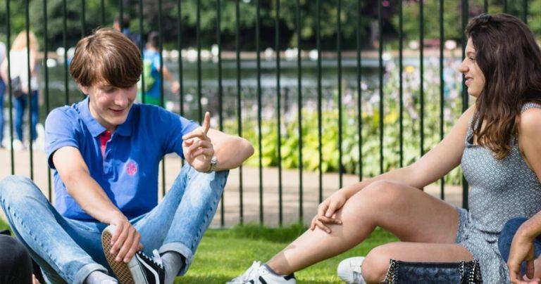 Grupo de jovens estudantes sentados em um parque, conversando