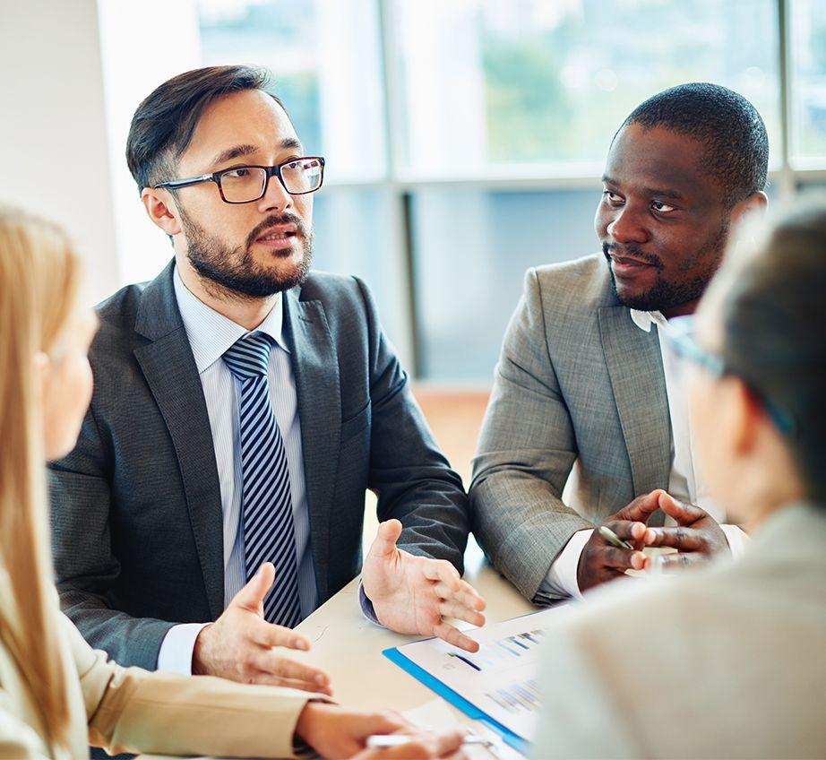 Homens de terno e mulheres conversando em uma mesa de conferência