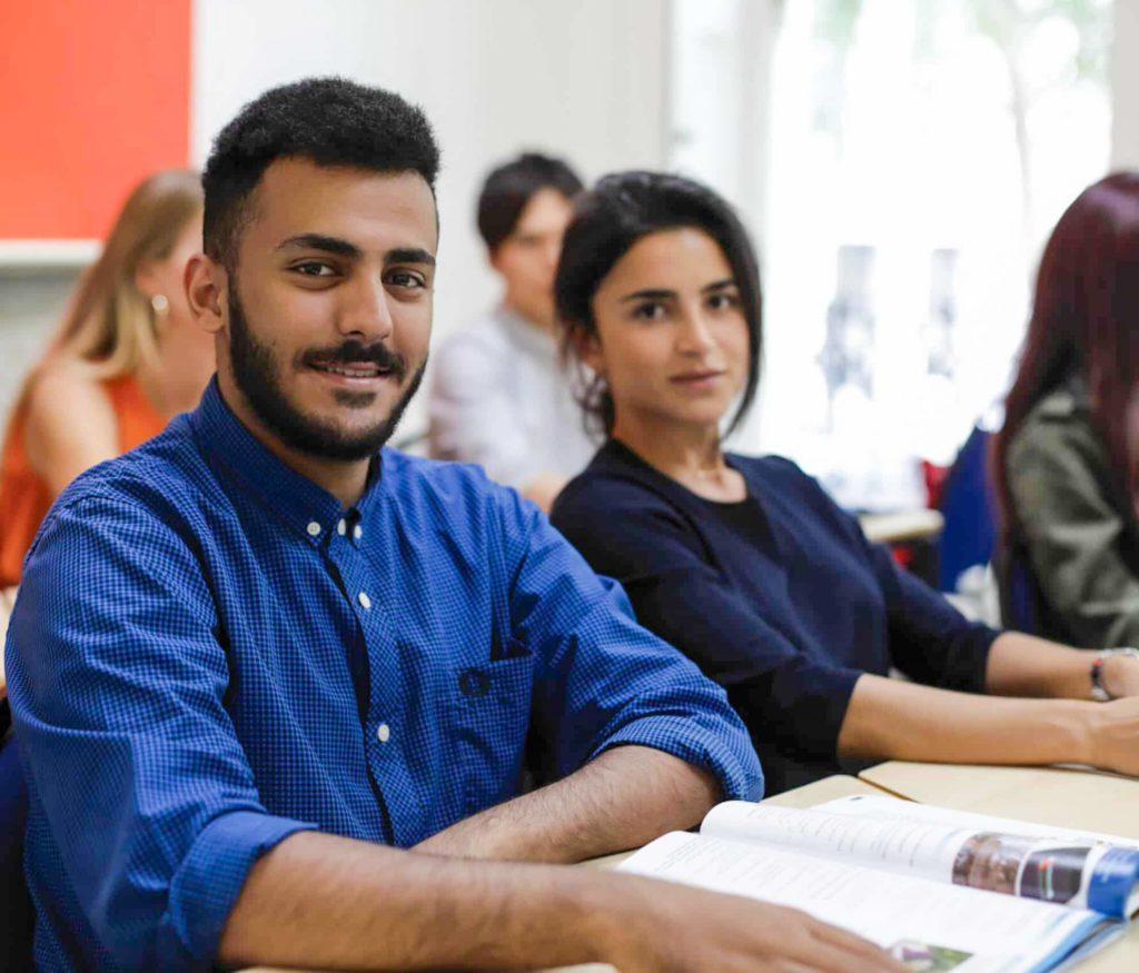 Dois estudantes em sala olhando para a câmara