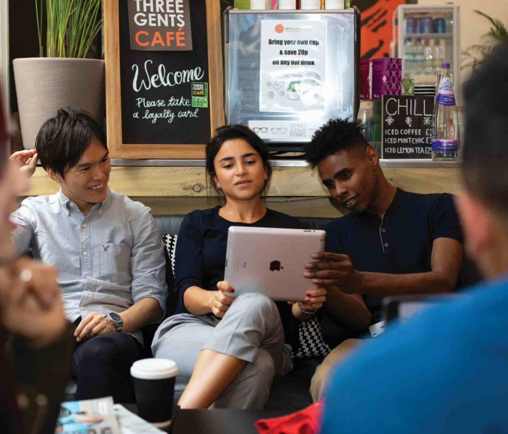 Três estudantes olhando para um laptop no café da BSC de Londres