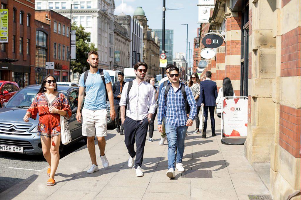 Grupo de estudantes caminhando por uma rua da cidade ensolarada