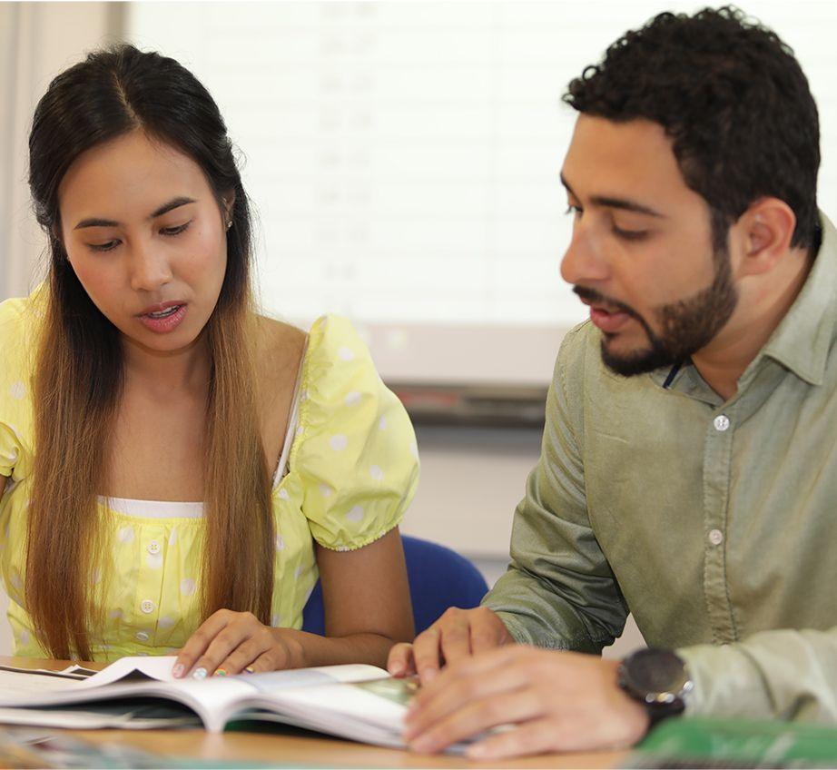 Um homem e uma mulher jovens sentados e compartilhando um livro didático