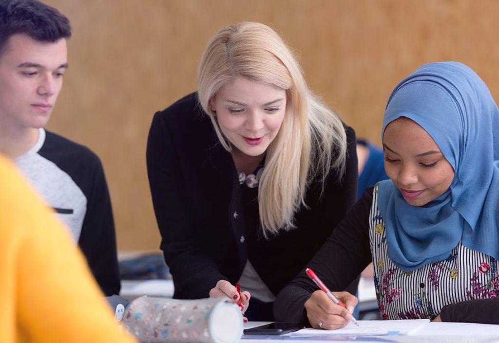 Um professor dá instrução a um estudante e sua colega observa