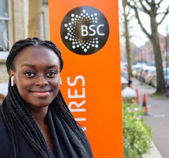 Jasmin parada em frente à placa da BSC Brighton
