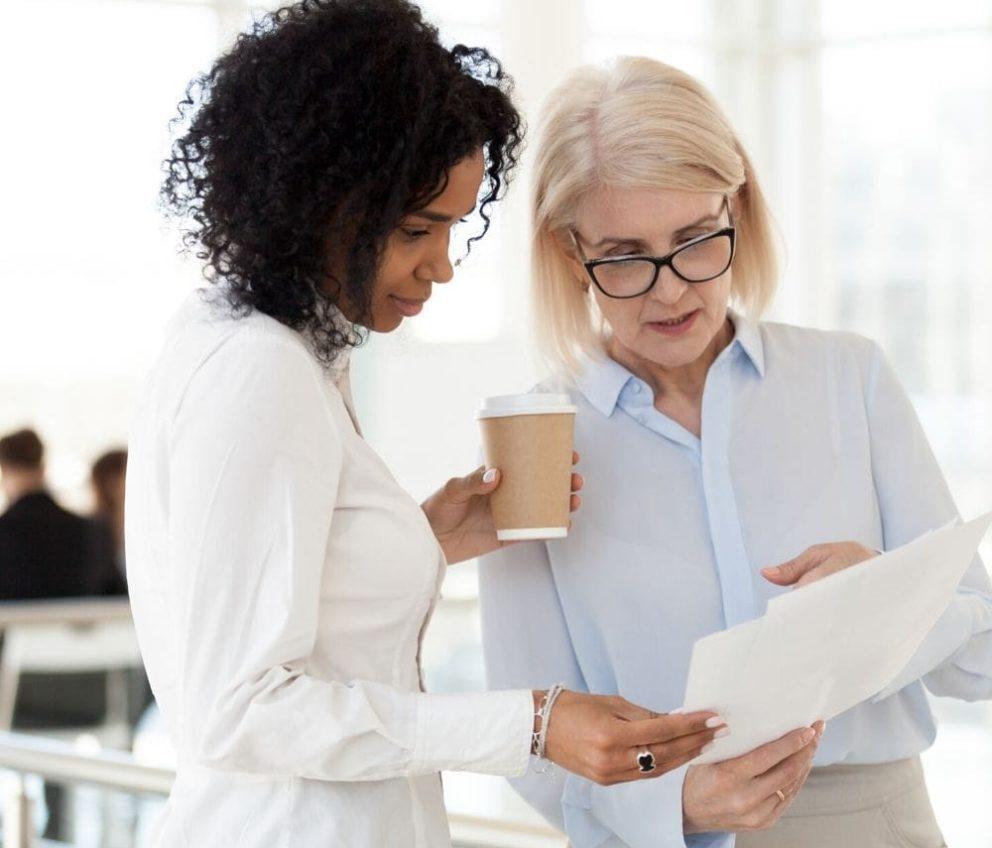 Duas mulheres no trabalho discutindo algo enquanto seguram um café