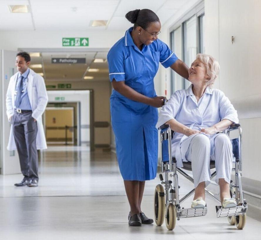 Uma enfermeira empurrando uma mulher idosa na cadeira de rodas