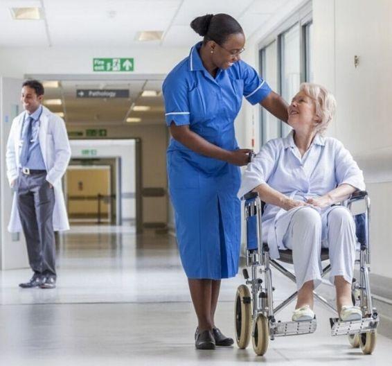 Enfermeira conversando com paciente em cadeira de rodas no corredor de um hospital
