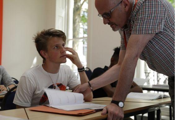 Professor falando com estudante em sala de aula