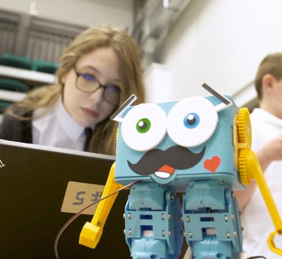 Uma garota com um notebook observa um robô no acampamento de verão de programação e robótica