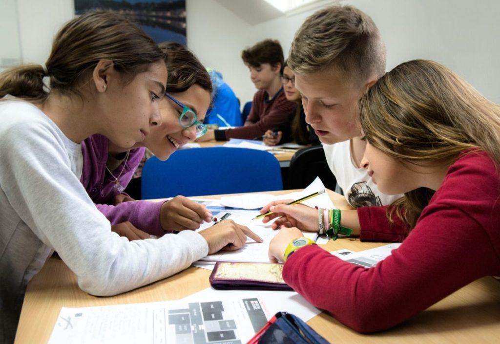 Quatro estudantes do acampamento de verão se inclinam sobre o meio de uma mesa, contribuindo para realizar um trabalho compartilhado