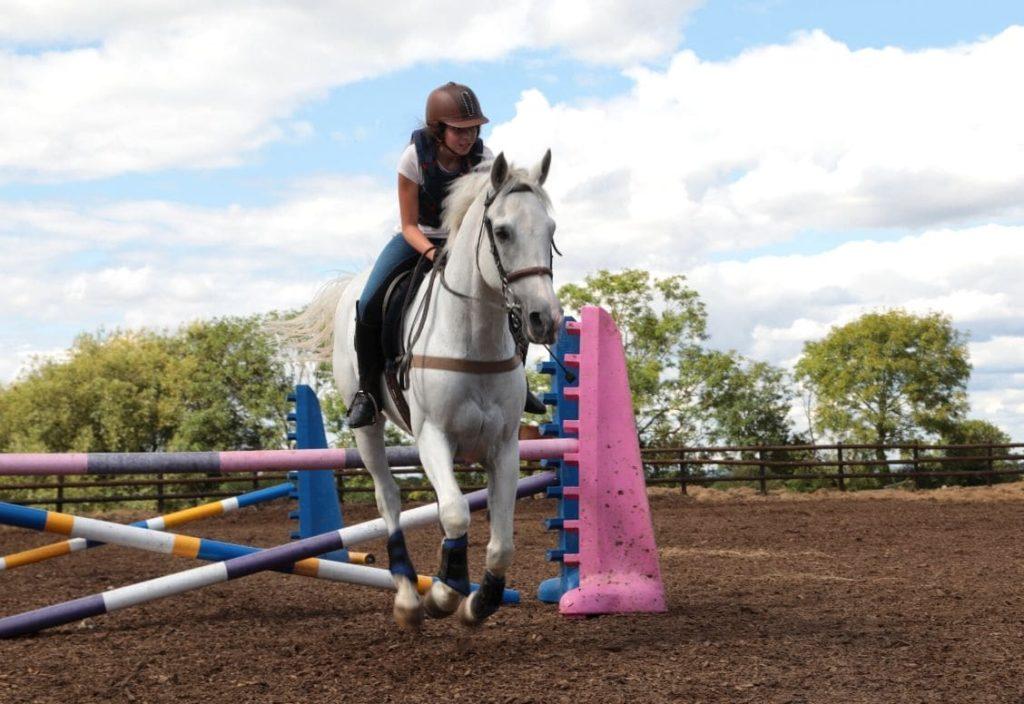 Garota a cavalo saltando sobre um obstáculo durante uma lição de equitação