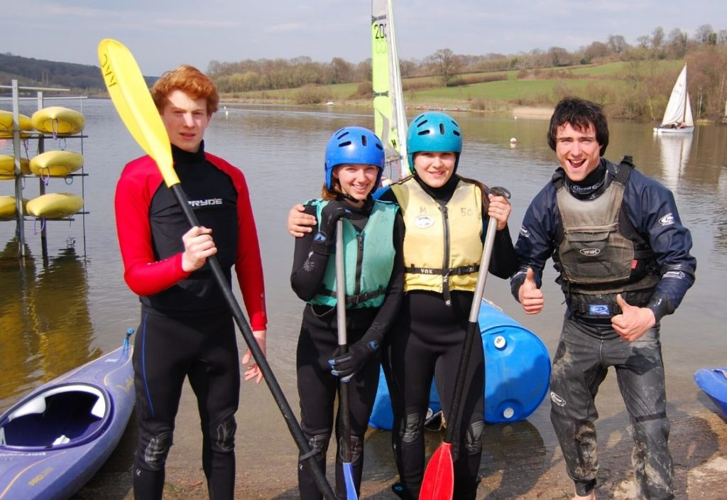 Três crianças e um instrutor em roupas de mergulho à margem de um lago, fazendo sinal de positivo com os polegares