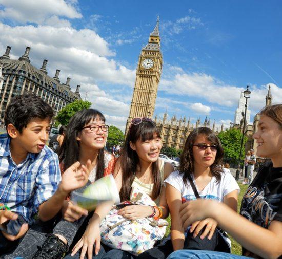 Jovens estudantes em um curso de verão de Londres, sentados ao ar livre em Westminster