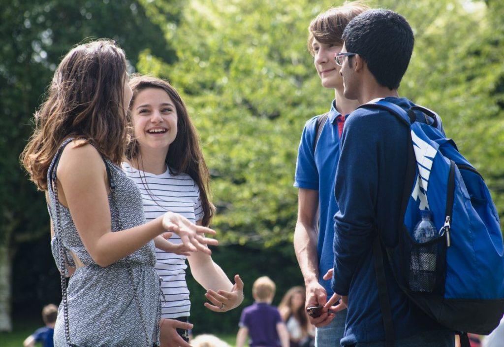 Quatro estudantes adolescentes de pé em um gramado e conversando