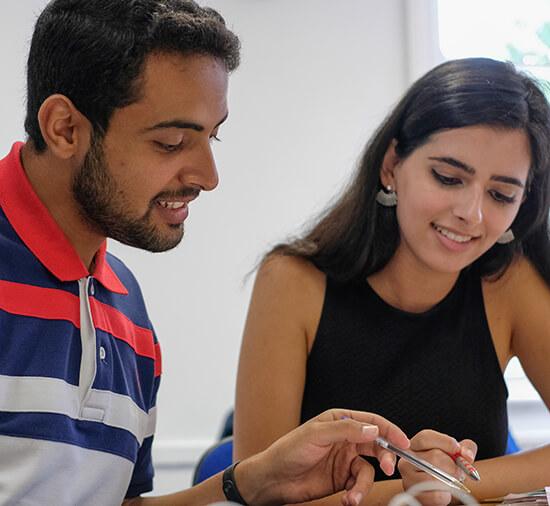 Alunos do sexo masculino e feminino sorrindo, enquanto olham para um livro do curso em sala de aula