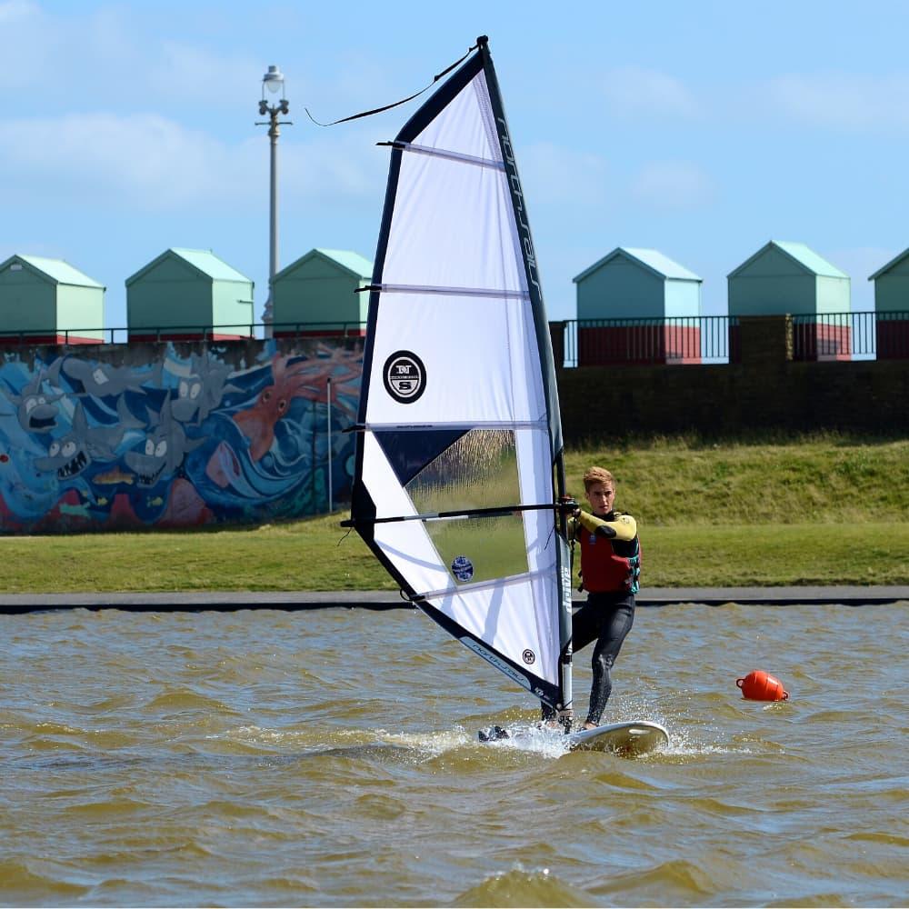 Pessoa praticando windsurf na lagoa
