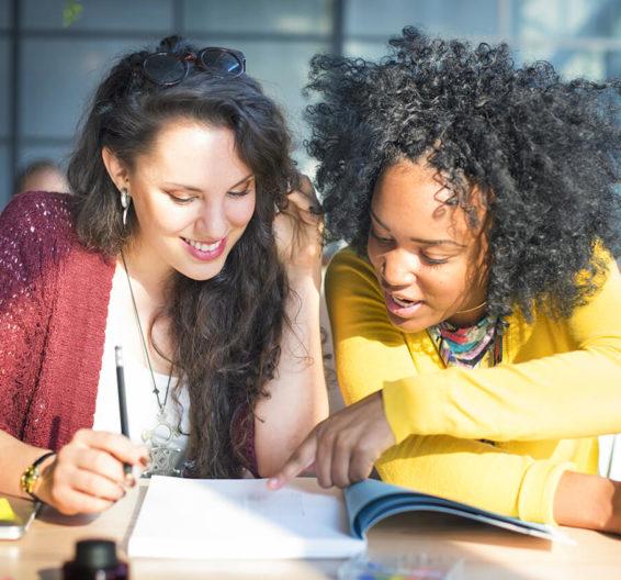 Duas estudantes maduras na aula, olhando para o caderno de trabalho