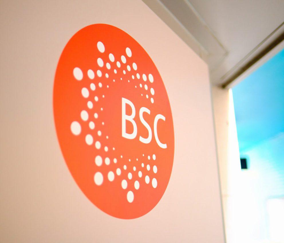 Изображение логотипа школ BSC на стене у окна